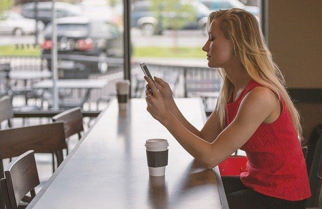 žena u baru s mobilem